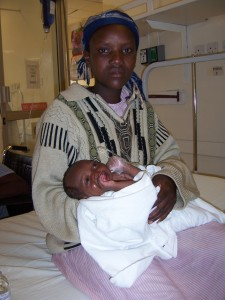 Local African woman holding her infant born with cleft lip and palate.